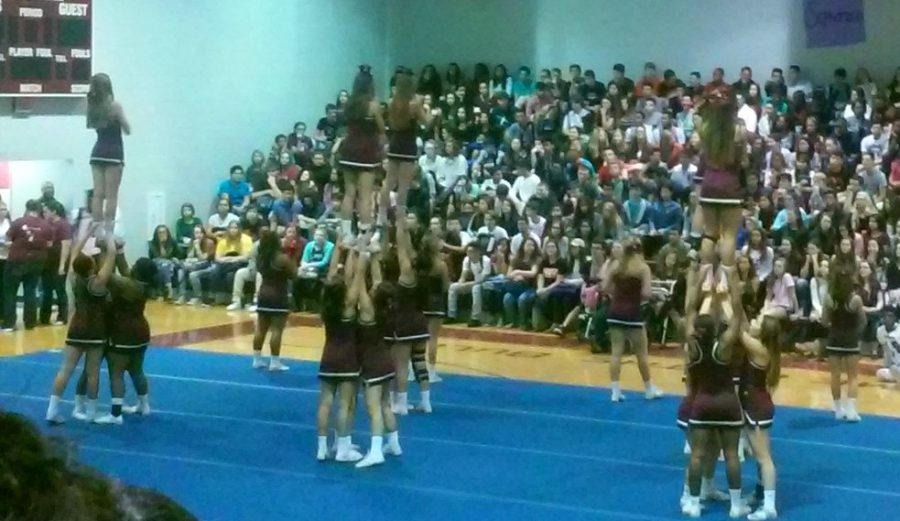 Cheerleaders perform as students eagerly watch.