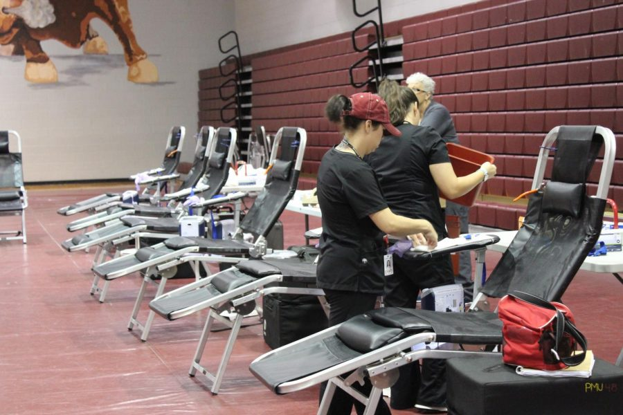 The staff is setting up before starting to take blood.