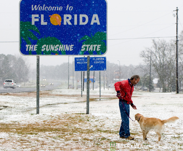 A man plays with his dog in the snow in Florida on US 231 at the Alabama State line south of Dothan.