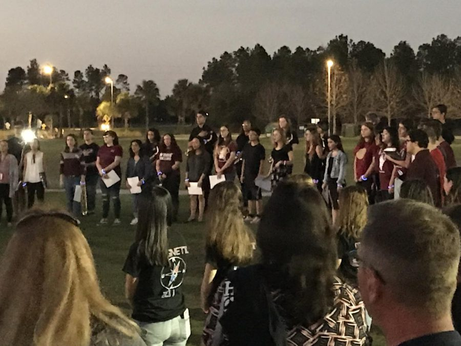 People come together at the Weasley Chapel fields  to honor the victims of the Parkland shooting.