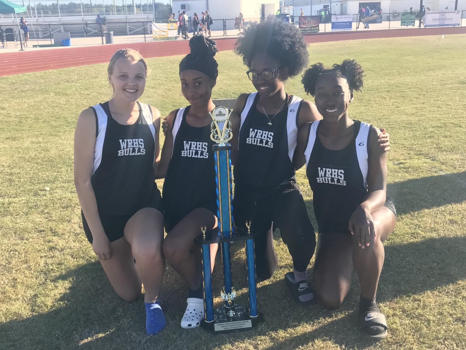 Bella, Sierra, Qyana, and Tai posing with the team's first place trophy.