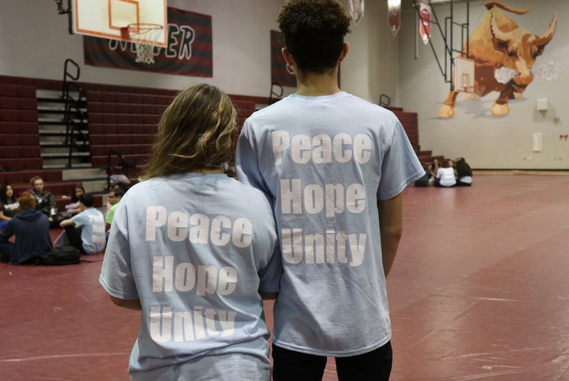 Two student facilitators at Unity Day wearing their club t-shirts