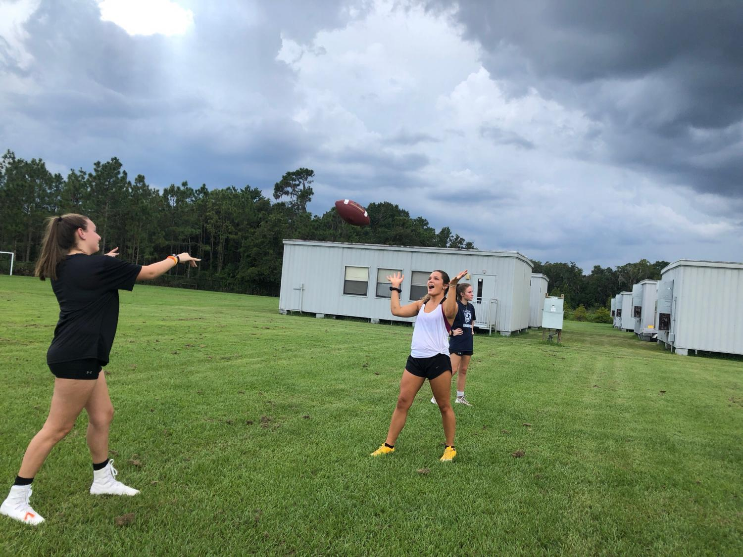 Seniors Jordyn Beer and Emily Beazley warming up their throws at practice Tuesday.