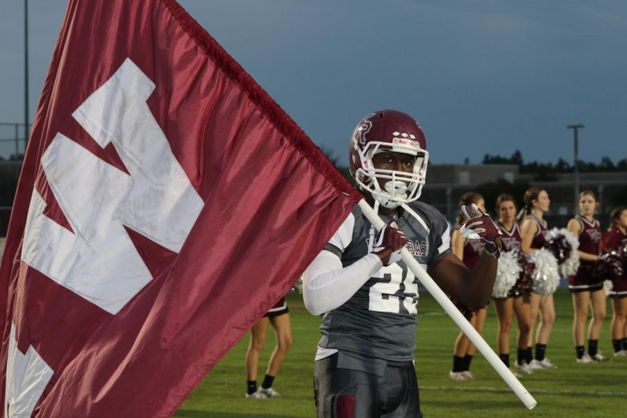 Senior Running Back, Mason Buie, leads the Bulls out of the tunnel waving the Wiregrass flag.