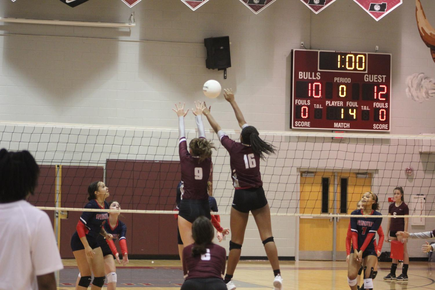 Zoi Evans (16) and Alexis Driggers (18) attempt a block.