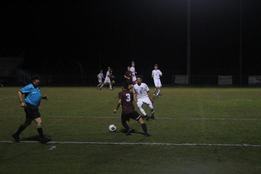 Junior Ryan Ahlf dribbling against a defender.