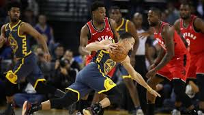 Raptors' point guard, Kyle Lowry, defends Warriors' point guard Stephen Curry as he attempts to drive to the basket.