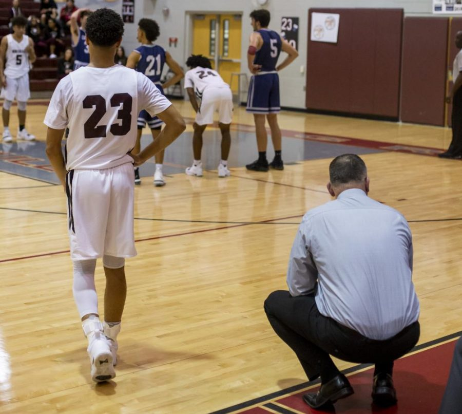 Coach Jeremy Calzone and Elijah Howell examining the court
