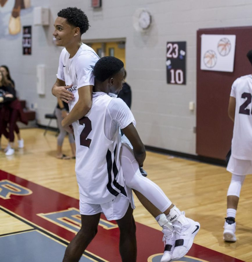 Elijah Howell celebrating his 1,000 point after the game with teammate Brian Parker.
