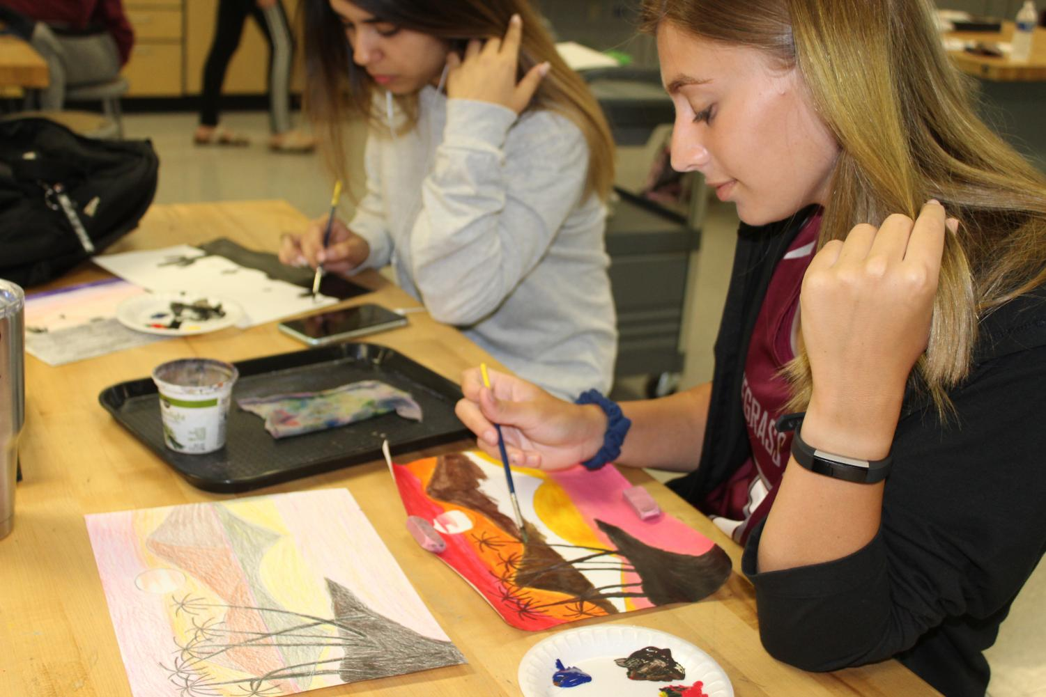 Sereen Mustafa and Carly Norman painting their landscape.