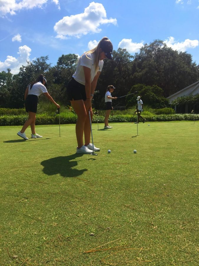 Senior Faith Drnec practicing her putting on the green before the match.