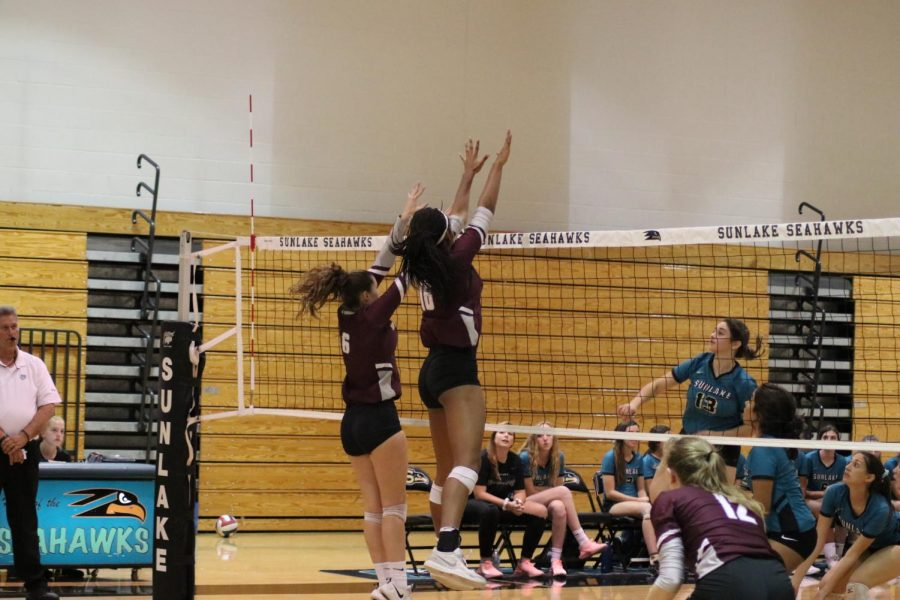 Junior, Zoi Evans blocking with one of her teammates.