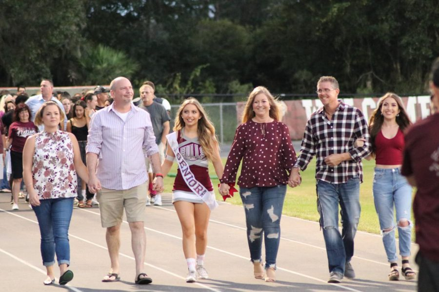 Macie Pickard with her family walking down the track with with big smiles on their face.