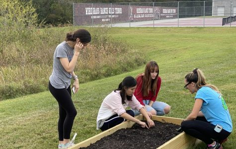 Hewitt assisting students planting seeds in the garden.
