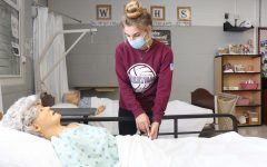 Senior CNA student, Holly Elfering, practicing her nursing skills on a mannequin.