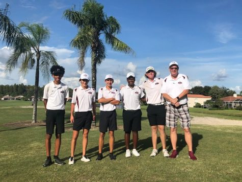 Coach Horrigan poses with boys varsity golf team at meet.