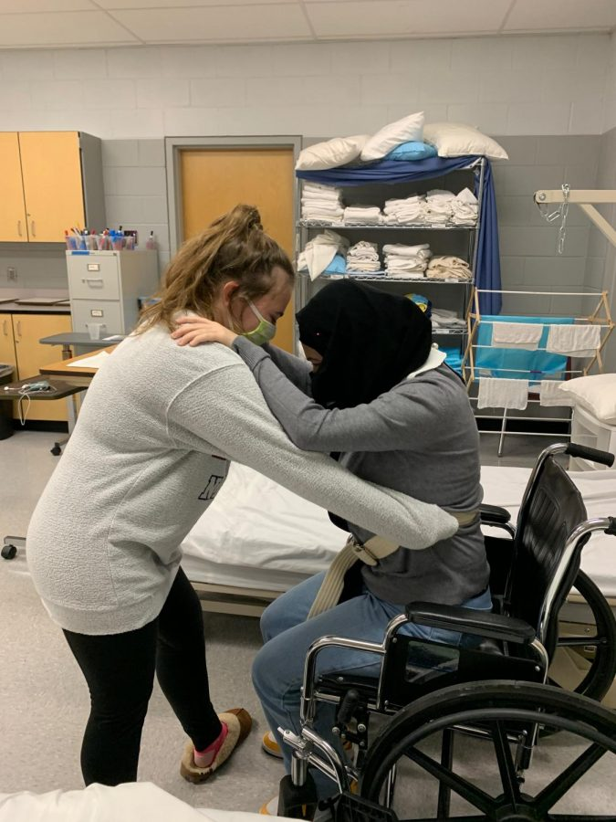 Seniors Rudaina Ouri and Bianca Nicholas practing the skill of moving a resident into a wheelchair.