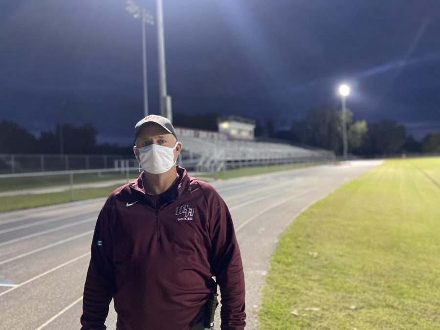 Athletic director and soccer coach, David Wilson, stands before an empty stadium.