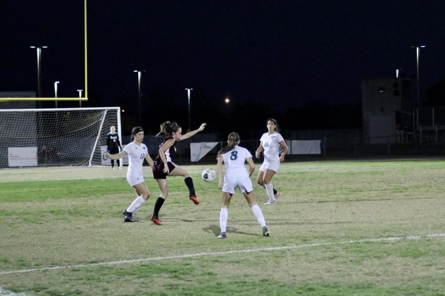 Taylor Pryor (4) clearing the ball to her teammates.