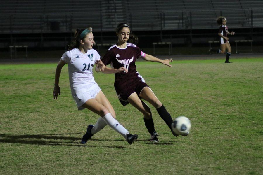 Kayla Ojeda and soccer captain (17) shields the ball.