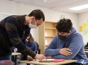 Easton Gorman helping sophomore Ethan Malave work through a problem during class.