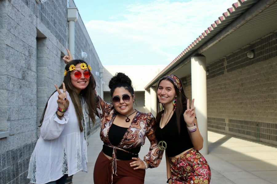 Newspaper+students+Daneila+Pena%2C+Isabella+Rey%2C+and+Nicole+Pi+pose+in+their+Hippie+Day+attire.